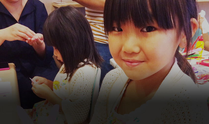 ワークショップでカメラに向かって微笑む子供の画像